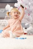Little girl at christmas. Little girl playing with mobilephone under christmas tree Stock Photos