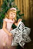 Little girl with Christmas snowflake Stock Photos