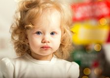 Little girl in christmas stands under a christmas tree in white Stock Photography