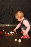 Little girl with Christmas toys against wall Stock Photo