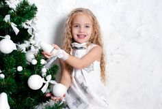 Little girl and Christmas tree Stock Images