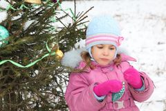 Little girl with Christmas-tree decoration Stock Photography