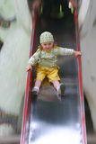 Little girl on chute. Little girl in colored clothing playing on playground Stock Images