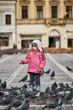Little girl in a city square feeding pigeons Stock Photos