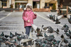 Little girl in a city square feeding pigeons Stock Photo