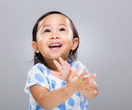 Little girl clap hand and look up Royalty Free Stock Photo