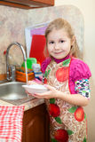 Little girl with clean plate at sink Royalty Free Stock Images