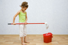 Little girl cleaning the floor Stock Images