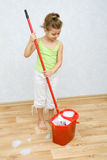 Little girl cleaning the floor Stock Image