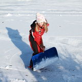 Little girl cleaning ice from snow on pond Stock Photo