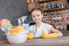 Little girl with cleaning supplies showing thumbs up at home Royalty Free Stock Photo