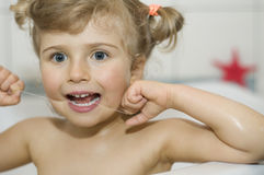 Little girl cleaning teeth by floss Royalty Free Stock Photography