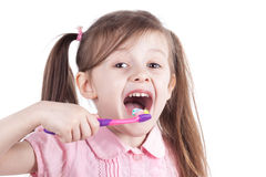 Little girl cleaning teeth with tooth brush. Isolated white background. Stock Photos