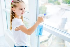 Little Girl Cleaning The Window Royalty Free Stock Images