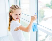Little Girl Cleaning The Window Royalty Free Stock Photos