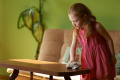 Little girl cleans dust cloth on  table Stock Photo
