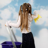 Little girl cleans sky. Little girl washes cloud on blue sky standing on stepladder with bucket and rag in hand - freshness and purity concept Stock Photos