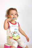 A little girl cleans teeth. A little girl cleans teeth and shows the mood Stock Photos