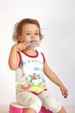 A little girl cleans teeth. Stock Photos