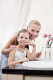 Little girl cleans teeth with her mother royalty free stock photo