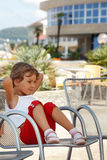 Little girl, clear summer day sitting in armchair. Beautiful little girl, clear summer day sitting in armchair on background of the hotel Royalty Free Stock Photo