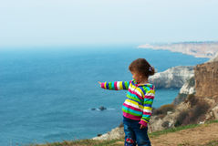 Little girl at the cliff to the sea. Royalty Free Stock Image