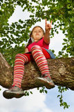 Little girl climbed on tree Royalty Free Stock Image