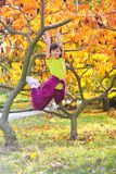 Little girl climbed on tree stock photos