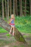 Little girl climbed on tree Stock Photos