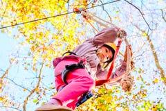 Little girl climbing in adventure park. Little girl is climbing in adventure park royalty free stock image