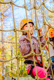 Little girl climbing in adventure park. Little girl is climbing in adventure park royalty free stock photography