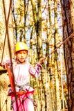 Little girl climbing in adventure park. Little girl is climbing in adventure park Royalty Free Stock Images