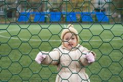 Little girl climbing a cell on a football field Royalty Free Stock Image