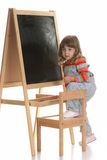 Little girl climbing on a chair Stock Images