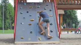 Little girl is climbing on climbing wall in the public playground. Little girl is climbing barefoot on climbing wall in the public playground stock footage