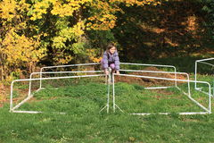 Little girl climbing on football wicket Stock Photo