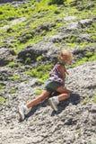 Little Girl Climbing On A Mountainside Royalty Free Stock Photos