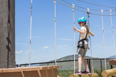 Little girl climbing on an outdoor ropes course. Horizontal photo with copy space Royalty Free Stock Photography