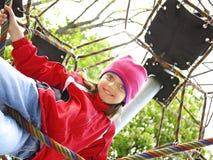 Little girl climbing on a playground Stock Photos
