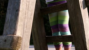Little girl climbing on a playground equipement stock video footage