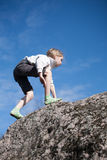 Little girl climbing the rock Royalty Free Stock Photos