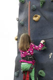 Little girl climbing rock wall at festival event stock image