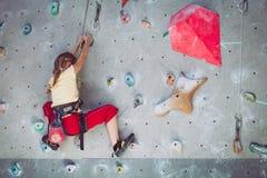 Little girl climbing a rock wall indoor Stock Photo