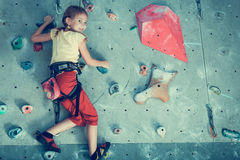 Little girl climbing a rock wall indoor Royalty Free Stock Photography
