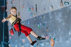 Little girl climbing a rock wall indoor Royalty Free Stock Photo