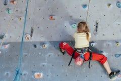 Little girl climbing a rock wall indoor Stock Image