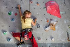 Little girl climbing a rock wall indoor. Concept of sport life stock image