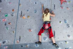 Little girl climbing a rock wall indoor. royalty free stock image
