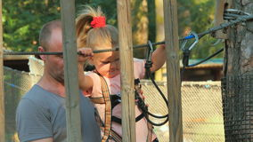Little girl climbing in rope park and spend her leisure time with father stock footage