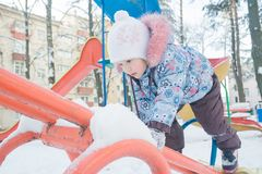 Little girl climbing on snowy playground seesaw. Little girl climbing on a snowy playground seesaw Royalty Free Stock Photos